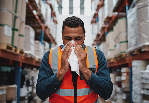 Warehouse worker blowing nose