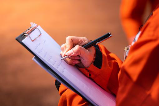 OSHA violations being written on a clipboard