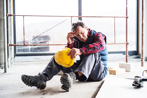 Accident of a male worker at the construction site with an injured head.