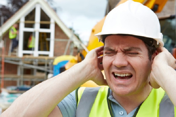 Construction worker covering ears in pain from noise