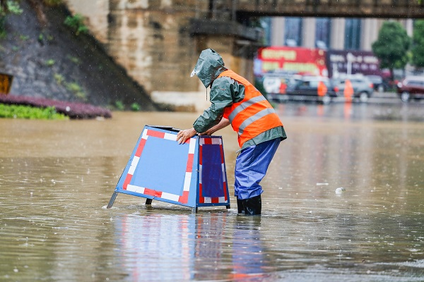Emergency crew worker placing a road sign on a flooded street in New York City